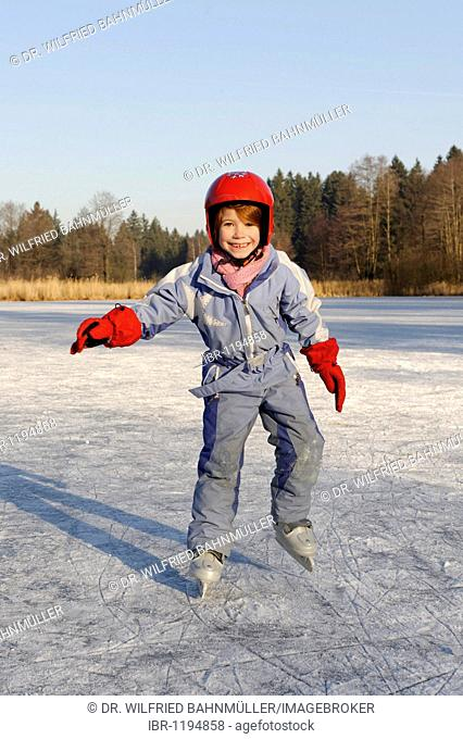 Girl wearing a helmet ice-skating on a little lake