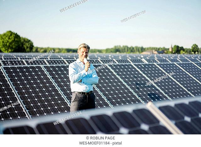 Mature man with smartphone standing in solar plant