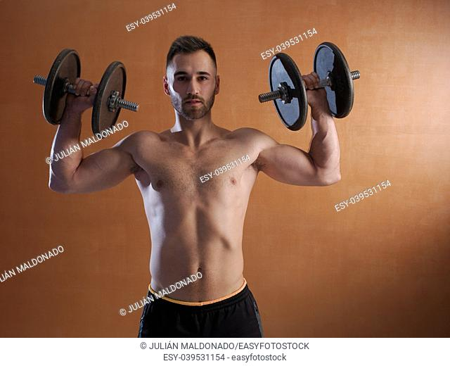 Young man training with weight lifting