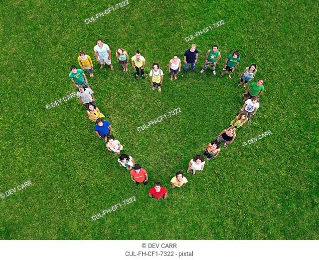 Group standing on grass in heart shape formation