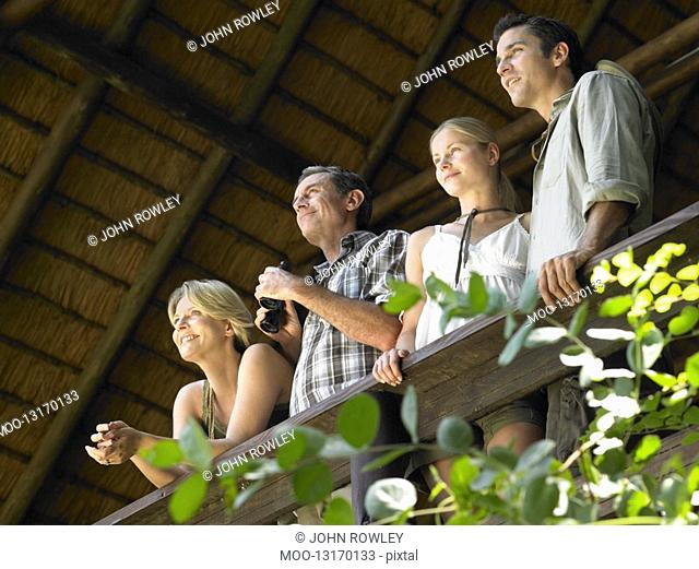 Four people looking at view from terrace man holding binoculars low angle view