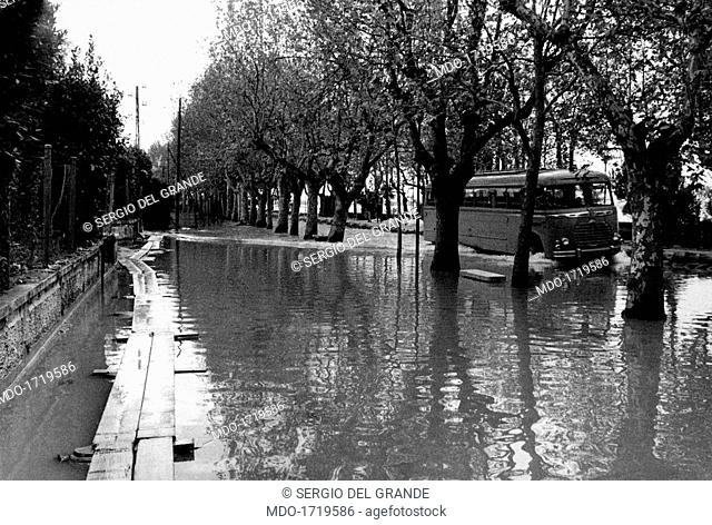 A bus on the flooded lakefront of Sirmione. A bus running along the flooded lakefront. Sirmione, November 1960