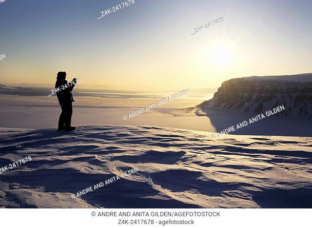 Expedition member looking over the frozen Tempelfjorden at sunset, Spitsbergen (Svalbard)