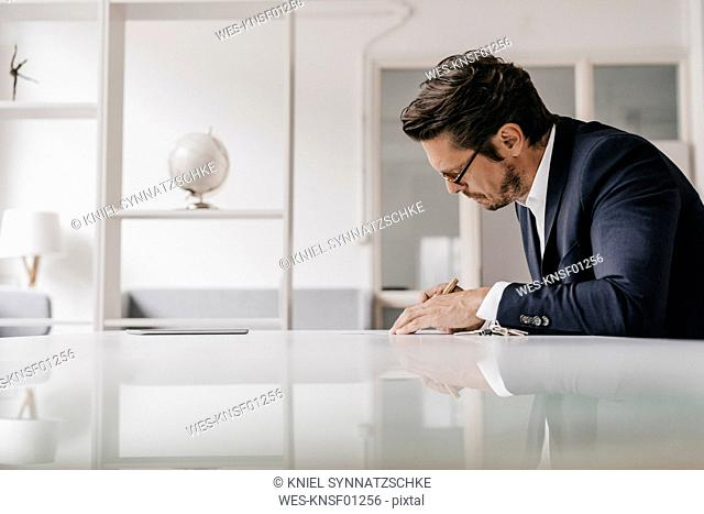 Businessman at table writing in notebook