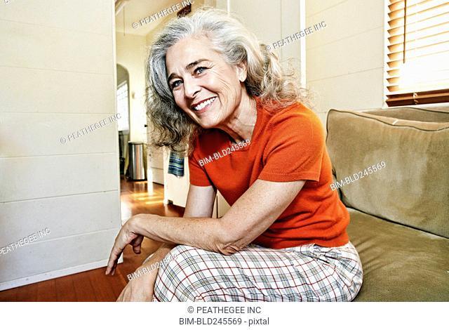 Portrait of older Caucasian woman sitting on sofa
