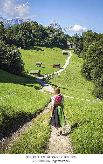 A girl in Typical Bayern dress walking in front of Wamberg village, with Mount Zugspitze and Waxenstein on the background