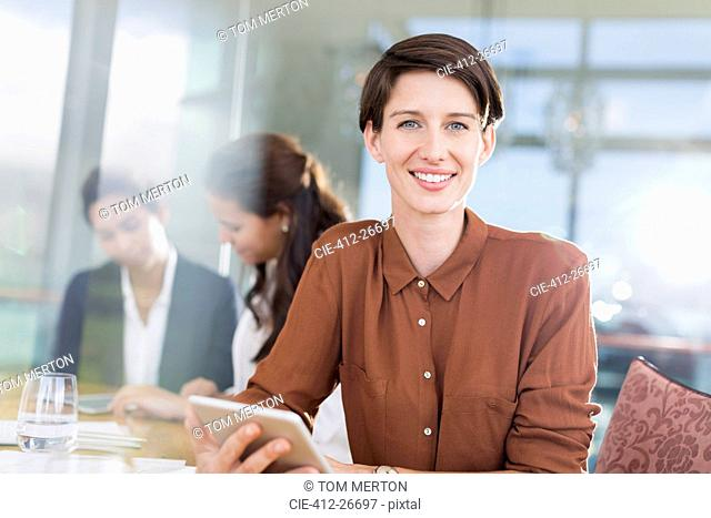 Portrait smiling businesswoman with digital tablet in office