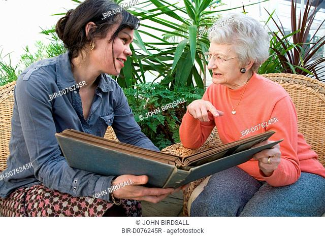 IndependentAge volunteer and older woman looking at an old photo album together