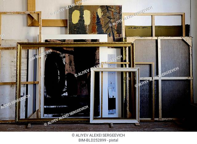 Paintings and frames leaning on wall