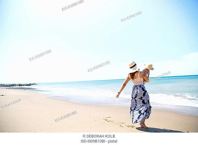 Rear view of mother carrying baby son on beach, Malibu, California, USA