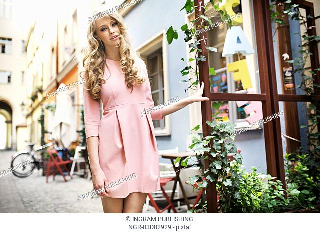 Tall and pretty young female model walking in old town
