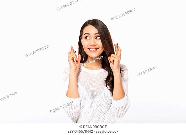 Portrait of a smiling asian businesswoman holding fingers crossed for good luck isolated over white background