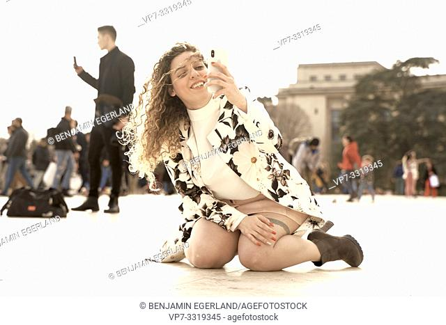 woman with phone kneeling on floor at Espl. du Trocadéro, in Paris, France, in Paris, France