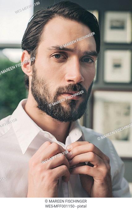 Portrait of young man buttoning the collar of his shirt