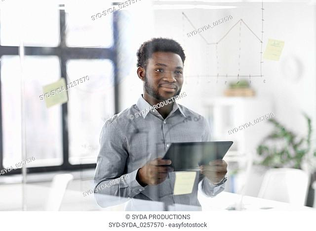 businessman with tablet pc at office glass board