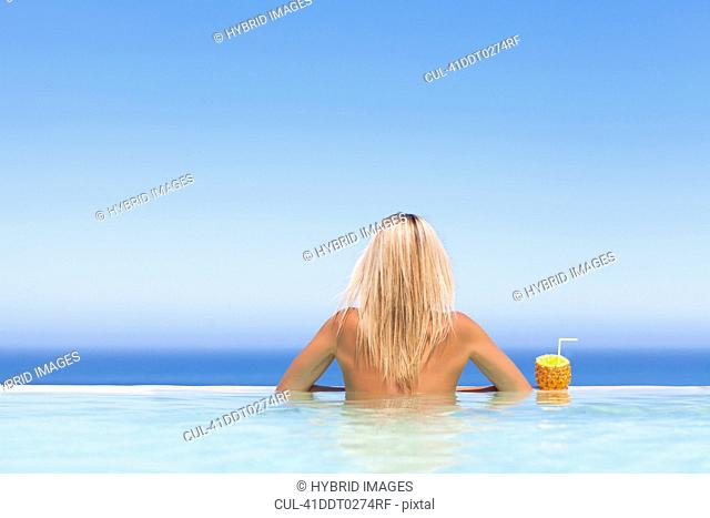 Woman relaxing with drink in pool