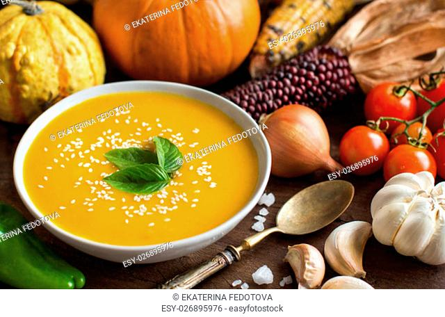 Fresh pumpkin soup with a spoon and vegetables on a wooden table
