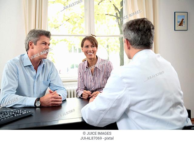 Doctor talking to couple in office