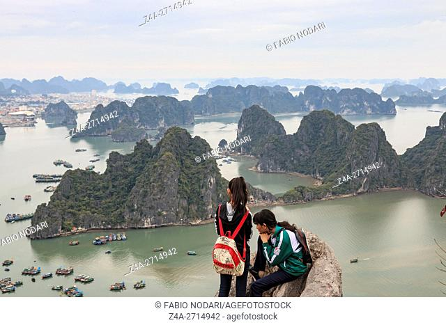 Young couple looking at Halong Bay and city from the top of Bai Tho Mountain