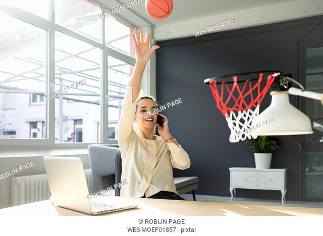 Freelancer on the phone throwing basketball into hoop in a loft