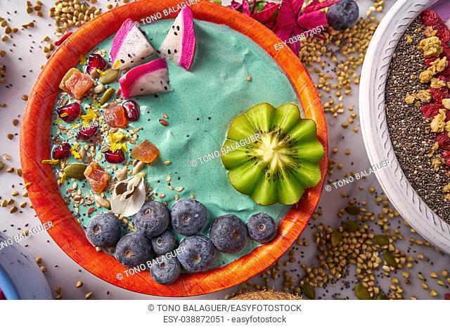 Acai bowl smoothie with kiwi blueberry seeds and pitaya dragon fruit