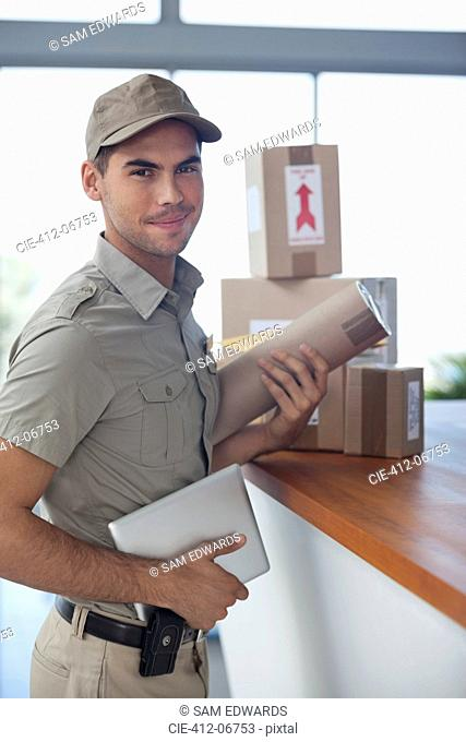 Delivery boy with packages in office