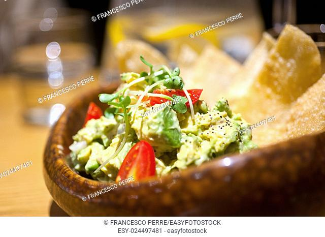 fresh avocado and shrimps salad with nachos on side