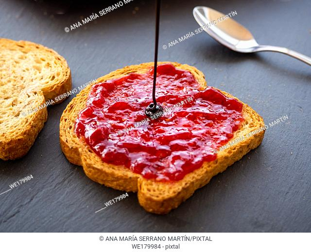 Pouring chocolate syrup on a slice of toast with raspberry jam