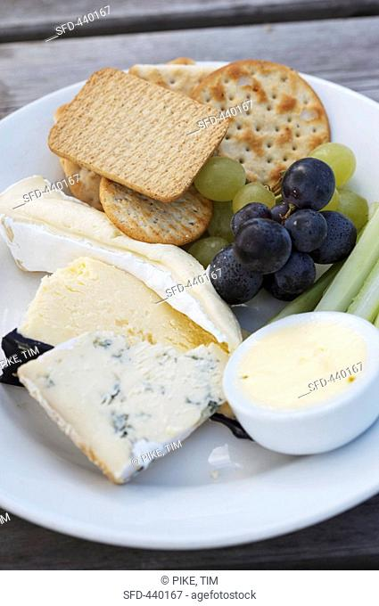 Cheese platter with crackers and grapes