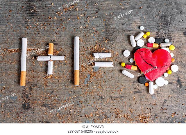Antismoking background. Diseased heart and pills on wooden surface