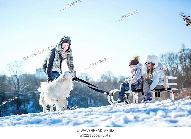 Father and children playing with sled