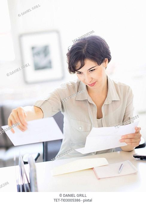Woman doing paperwork at home office
