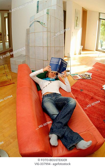 Young woman lying on a couch and reading a book. - 05/11/2006
