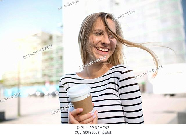 Young woman with blond flyaway hair with takeaway coffee