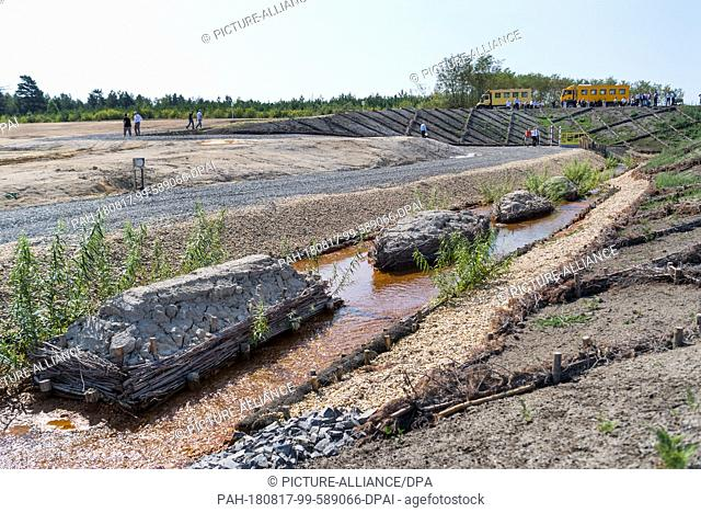 17 August 2018, Gemrany, Weisswasser: Water flows down an inlet ditch, taken at the press event on the occasion of the start of the flooding of Lake...