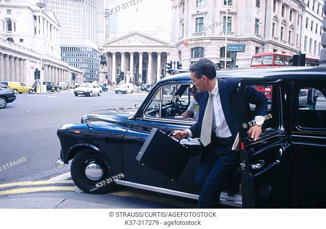 Businessman getting out of taxi cab in financial district. City of London