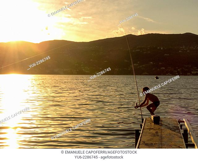 Boy fishing on a pier for small boats, sunset, Lake Maggiore, Ranco, Lombardy, Italy