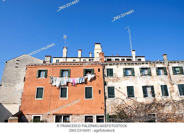 Woman put clothes hanging at sun. Venice, Veneto. Italy