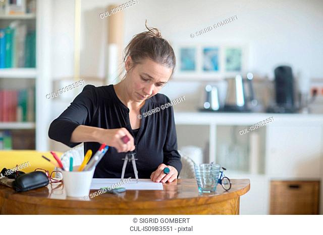 Mature woman sitting at desk, using pair of compasses