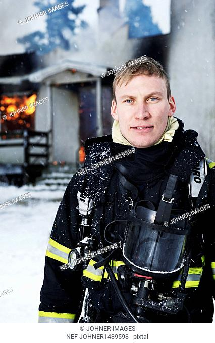Portrait of firefighter in front of burning house