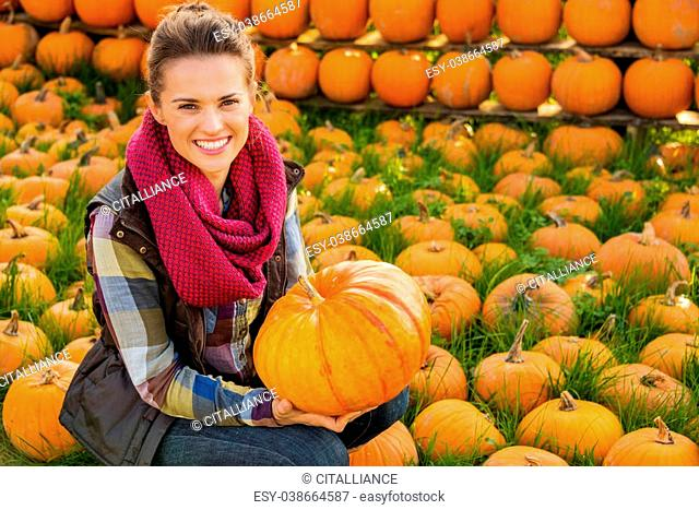 Portrait of smiling woman sitting and holding big pumpkin on farm during the autumn season
