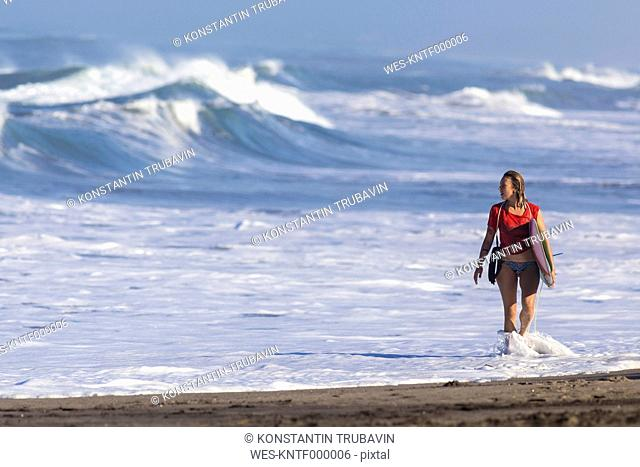 Indonesia, Bali, woman carrying surfboard at seafront