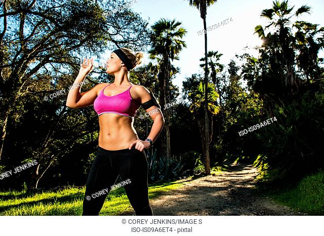 Young woman exercising in forest drinking mineral water