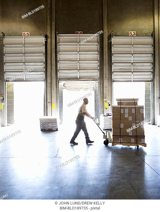 Warehouse worker pushing pallet of boxes