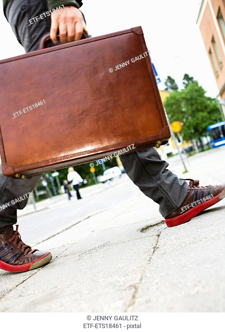 Man wearing sneakers and carrying a briefcase, Sweden