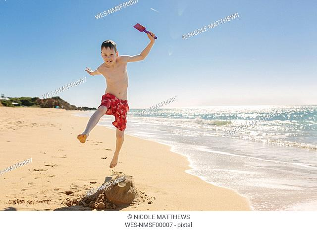 Boy playing and jumping on the beach
