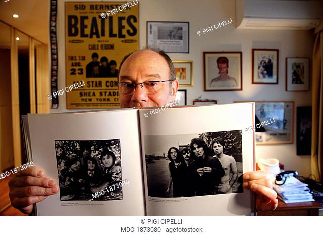 The director and actor Carlo Verdone showing a picture from the catalogue Beatles to Bowie for a photo shooting at home. On the wall behind him