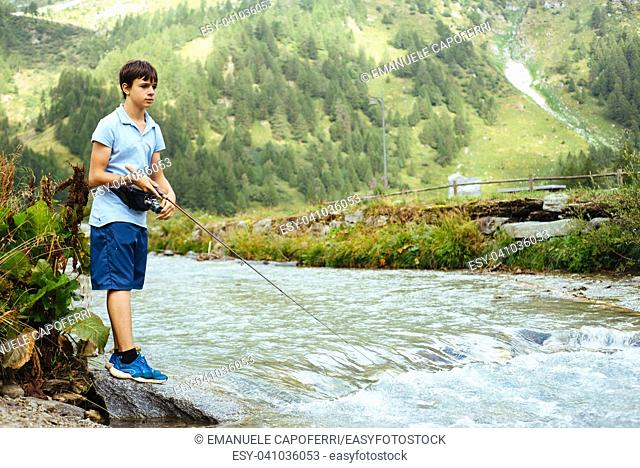 14 year old boy fishing in a mountain river