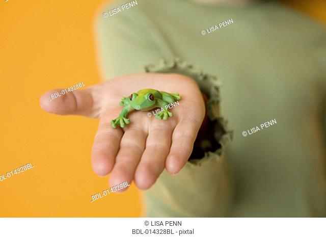 close-up of child's hand with green frog