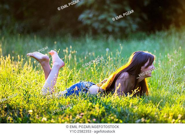 Lying happy barefeet in grass young woman warm light